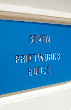 stencil design of 'SEVEN PRINTWORKS HOUSE' on blue