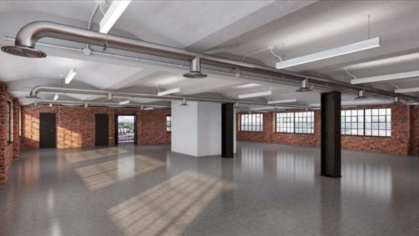well lit open leasehold workspace with grey floors, brick walls and square French windows