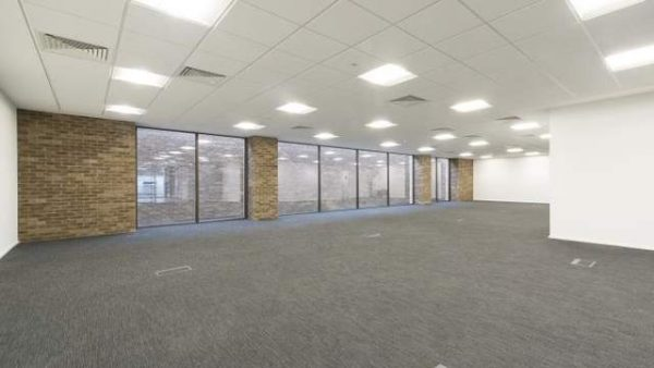 office space with white walls, brick structuring, floor to ceiling windows and a grey carpet