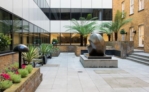 courtyard lined with flowers, benches in between, potted plants and trees, impressive sculpture in the centre