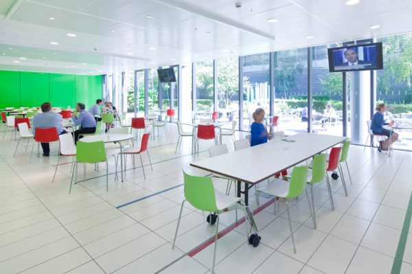 lunching area with television on, informal chats going on round tables and alternating red and green chairs