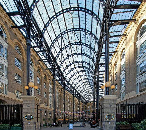 zig zag bunting outside a strip of buildings with transparent arched roof enclosing the wide impressive promenade