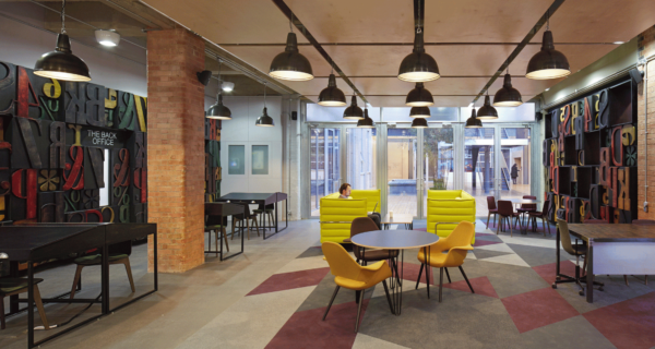 trendy break out space with desks, tables and chairs, shapes in the carpet, brick pillars and black walls covered in big colourful stencilled letters