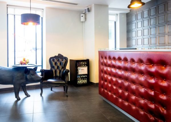 reception waiting area with pinned leather upholstery, drinks fridge and table shaped like a pig carrying a tray of apples