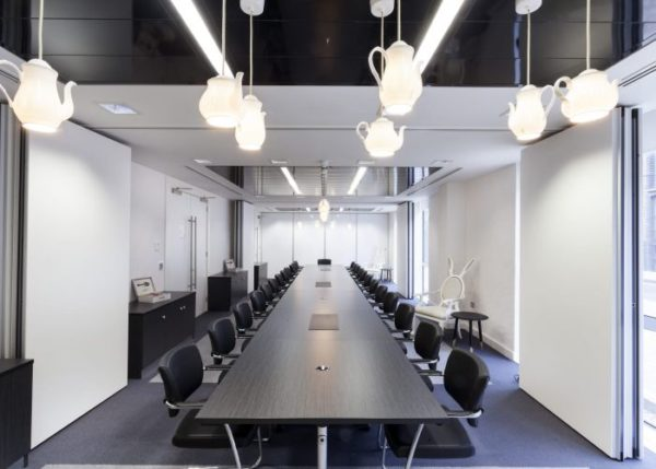 meeting or conference room with long table and chairs either side with hanging glowing teapot lamps and a white rabbit themed chair to one side