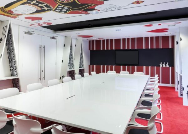 Alice in Wonderland style meeting room with white table and chairs, red carpet, white 'house of cards' walls, white rabit figurines and Queen of Hearts and Two of Hearts cards on the ceiling