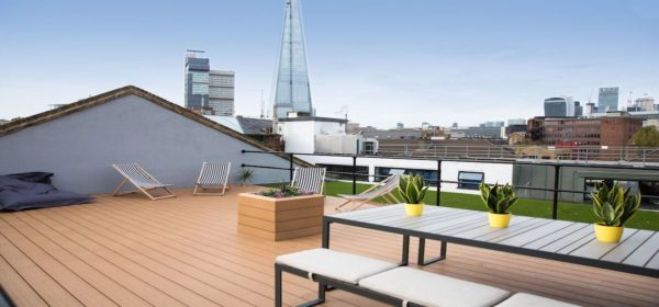 open roof terrace with beanbag wooden decking, deck chairs, table and bench, cool pot plans and rooftop view of the Shard