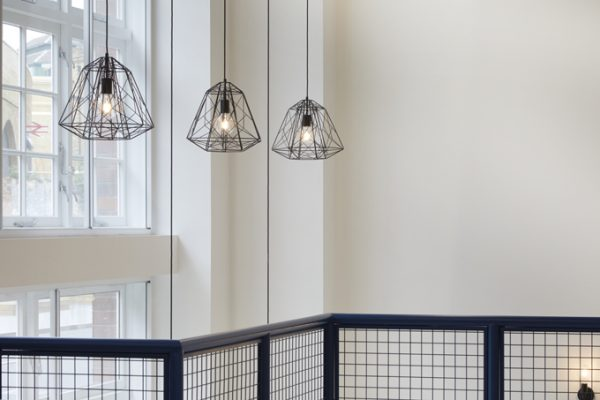 stylish spiderweb metal framed hanging lamps and dark blue rail in lightwell