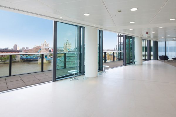 clean white riverside office with windows opening onto a balcony overlooking the Thames and nearby Tower Bridge