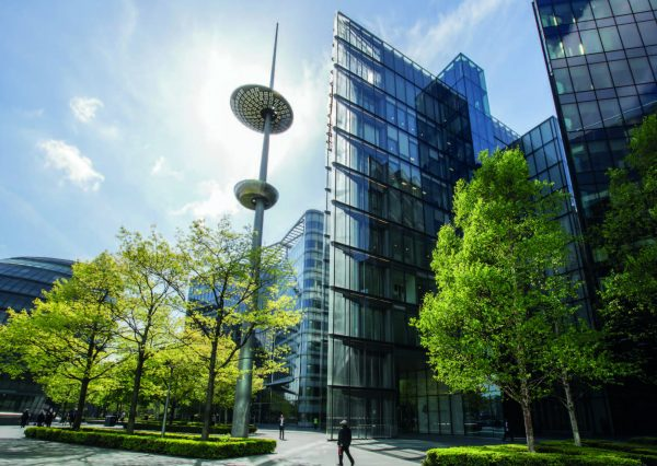 spectacular glass buildings and green trees bordered by low hedges outside and open walkways on a sunny day