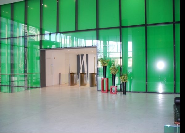 bright green glass panelled wall with opening allowing access through entrance barriers, tall vases of flowers to the side