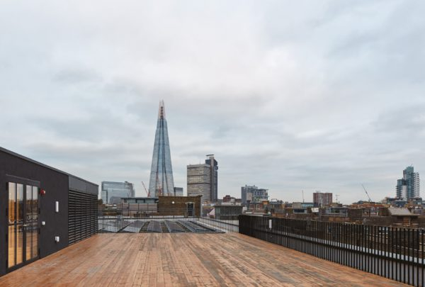 large rooftop terrace with worn looking deck offers views over Borough and beyond on a cloudy day