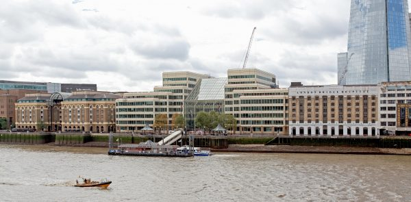 London Bridge City pier infront of the Cottons Centre Building with London Bridge Hospital next door watching river boats zooming past