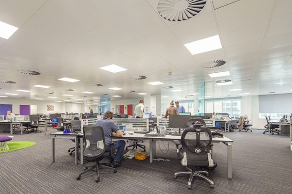 open grey carpeted office with ventilation fans and light panel in the ceiling and staff busy working round desks