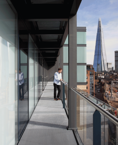 an outside balcony offers a view of the busy street and railway line below, with the Shard dominating the views further