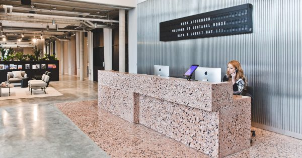 "polished reception in peach marble effect and letters mounted behind receptionist ""GOOD AFTERNOON WELCOME TO TINTAGEL HOUSE HAVE A LOVELY DAY!!!"""