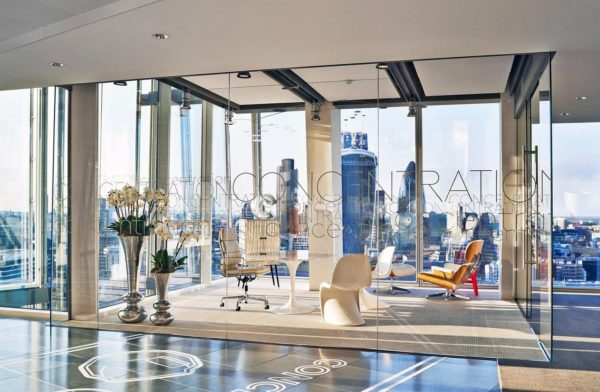 meeting room with trendy vases of flowers and furniture, 'CONCENTRATION' glass walls and view of London's city skyscrapers in the background