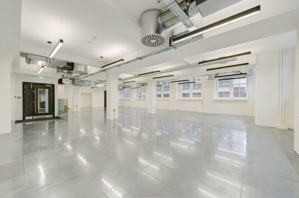 shiny polished floor of airy leasehold office painted white with lamps and natural light